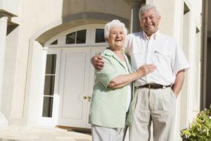 Senior couple standing outside house
